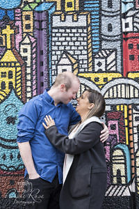 Couple embracing in front of a wall od graffiti