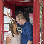 Couple standing in a reb phone box, looking into each other eyes
