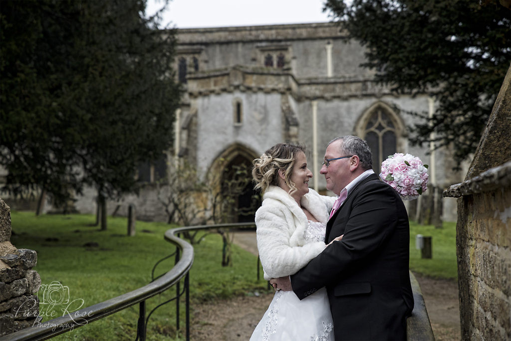 bride and groom embracing outside of their church
