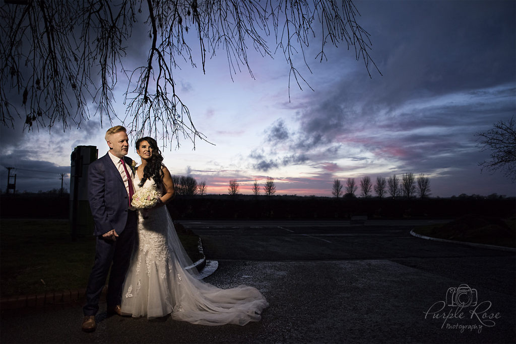 Bride and groom stood in front of a sunset