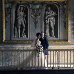 Bride and groom embracing on a balcony
