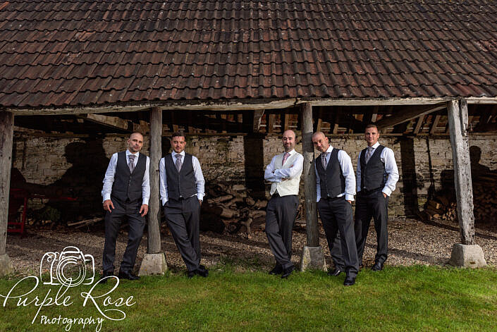 Groomsmen standing in a barn