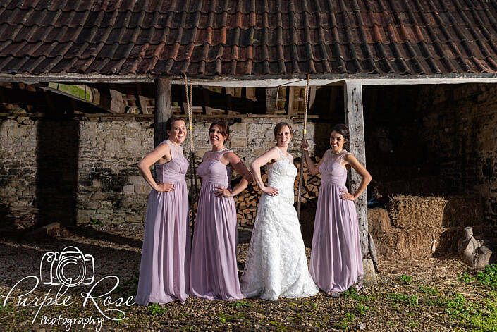 Bride and bridesmaids standing in a barn