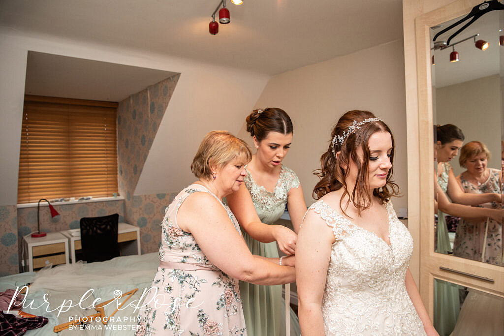 Brides family lacing her dress