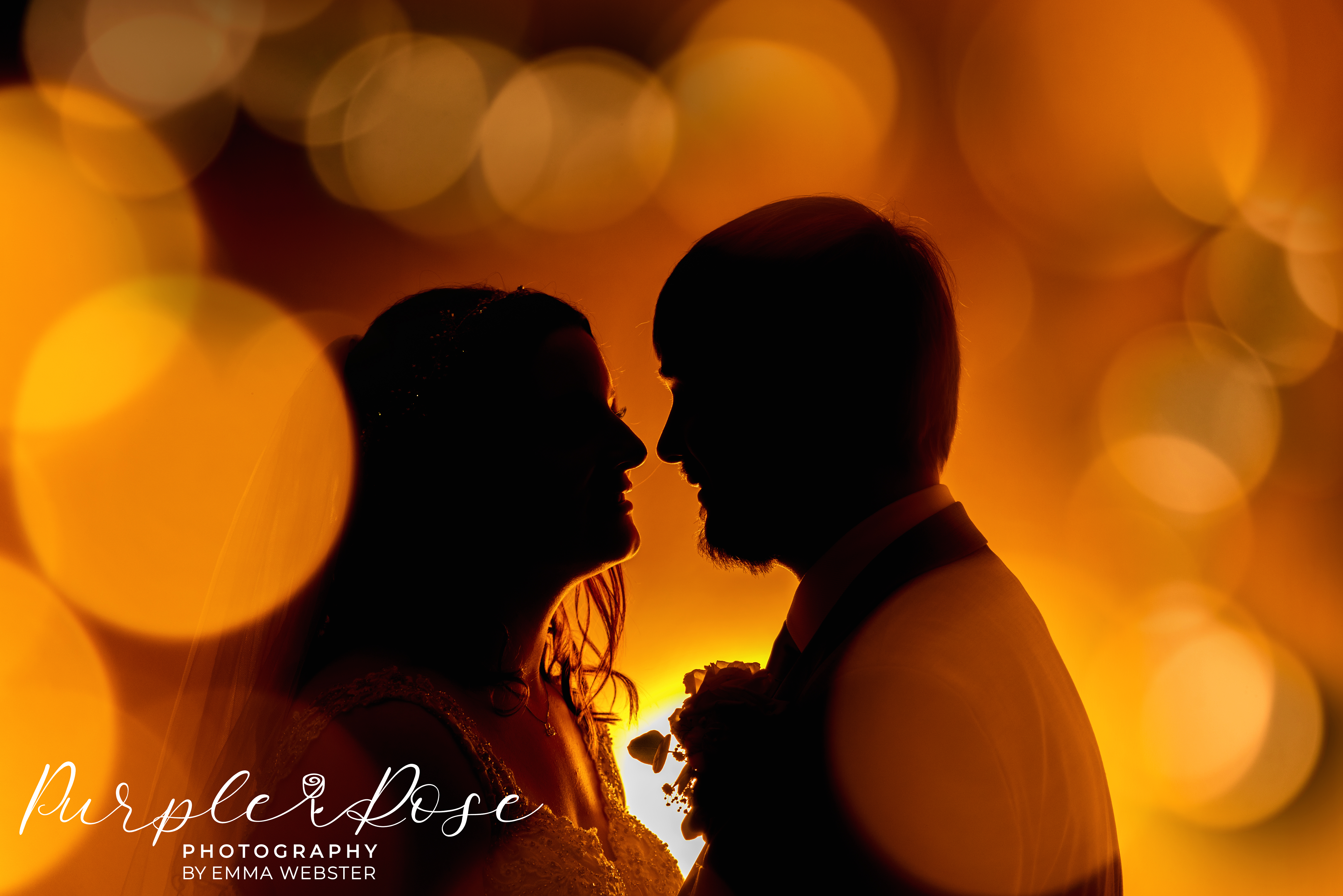 Siloueete of bride and groom surrounded by orange balls of light