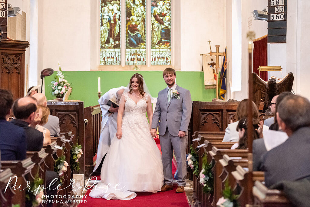 Bride and groom hand in hand at the church