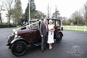 Bride and Groom with their wedding car