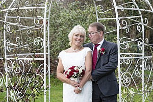 Bride and groom embracing in the gardens