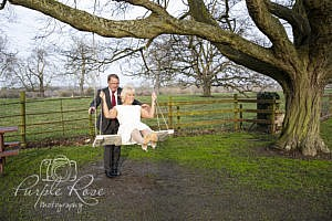 Groom pushing his bride on a swing