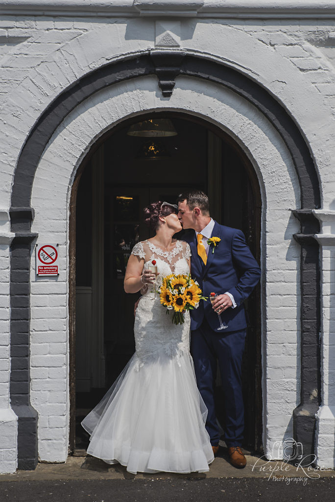 Bride and groom kissing in front of wedding venue
