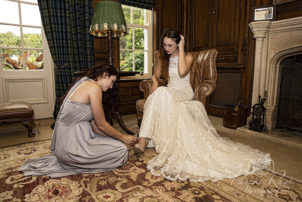 Bridesmaid helping bride put her shoes on