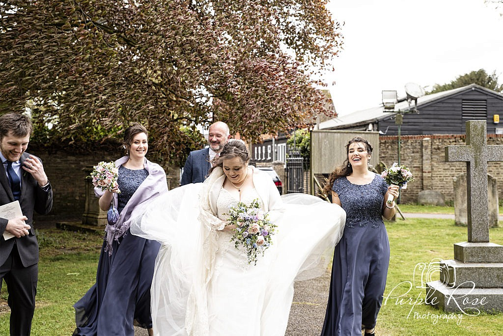 Bridal party walking to the church on a windy morning