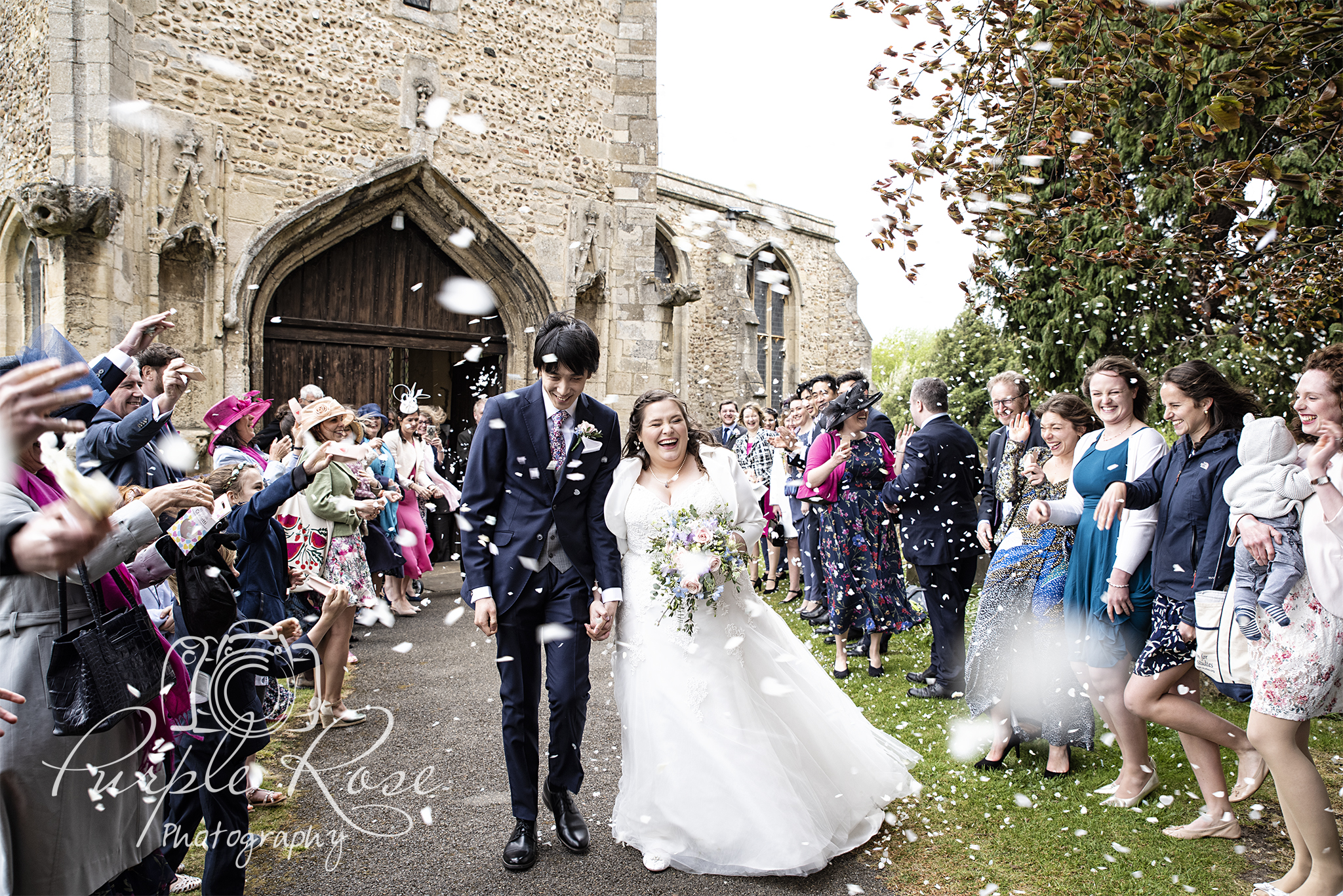 Bride and groom being showered in confetti as they leave the church
