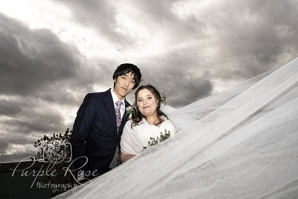 Bride and groom in front of a dramatic sky