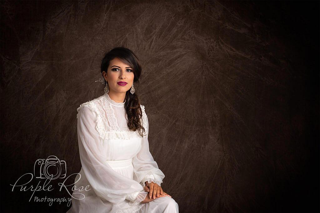 Photo of woman sitting in vintage wedding dress