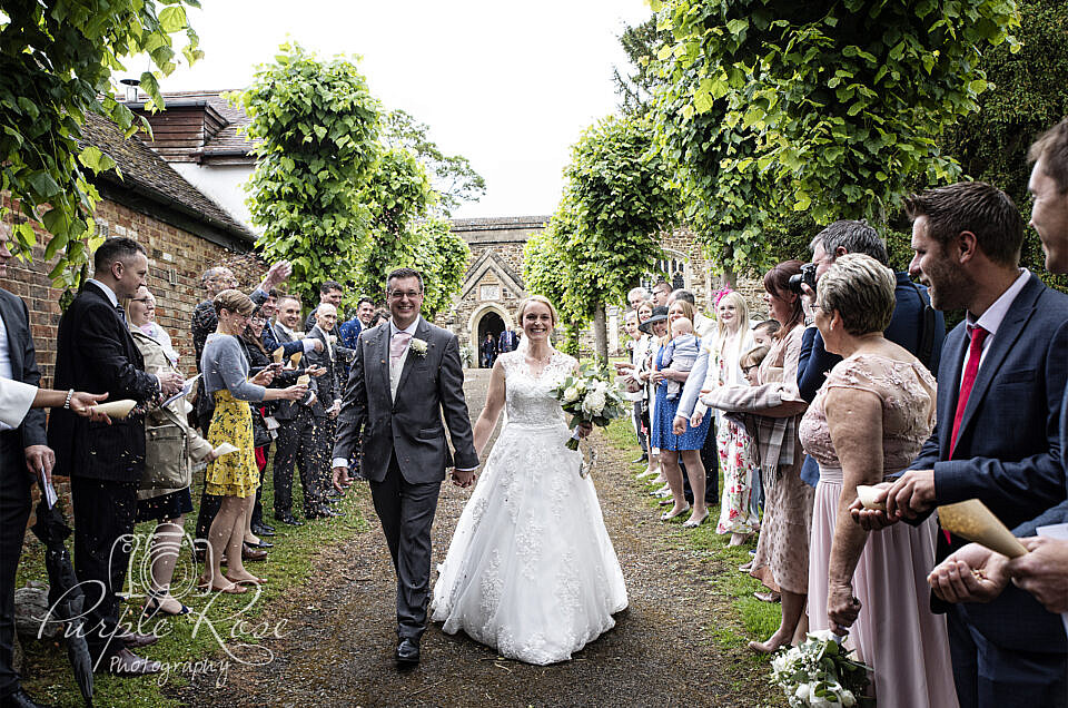 Bride and groom walking as guests throw confetti