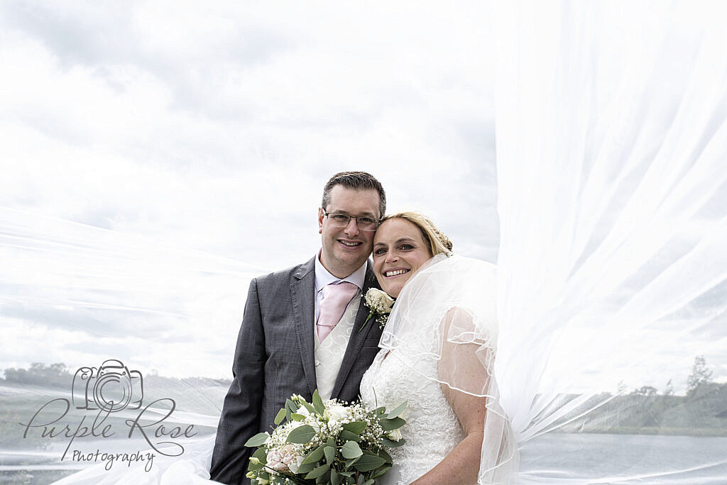 bride and groom in front of a cloudy sky