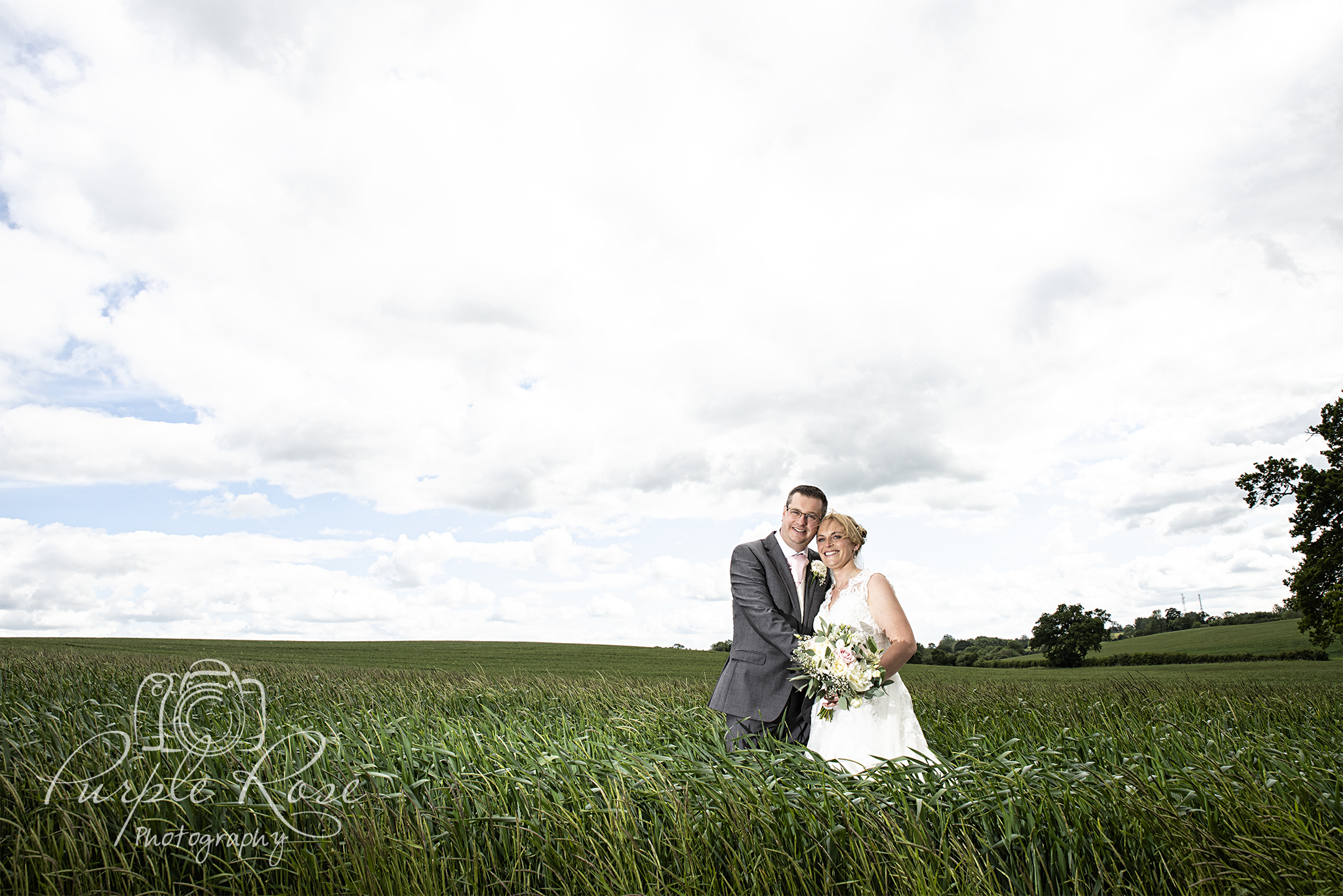 Bride and groom standing in a field