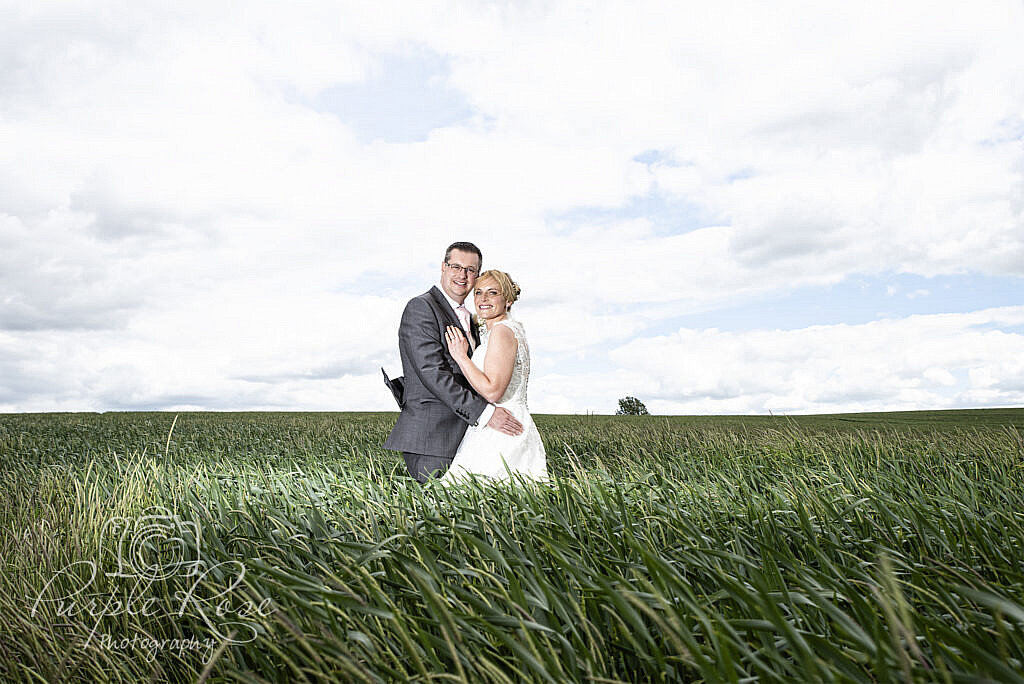Bride and groom embracing on a field