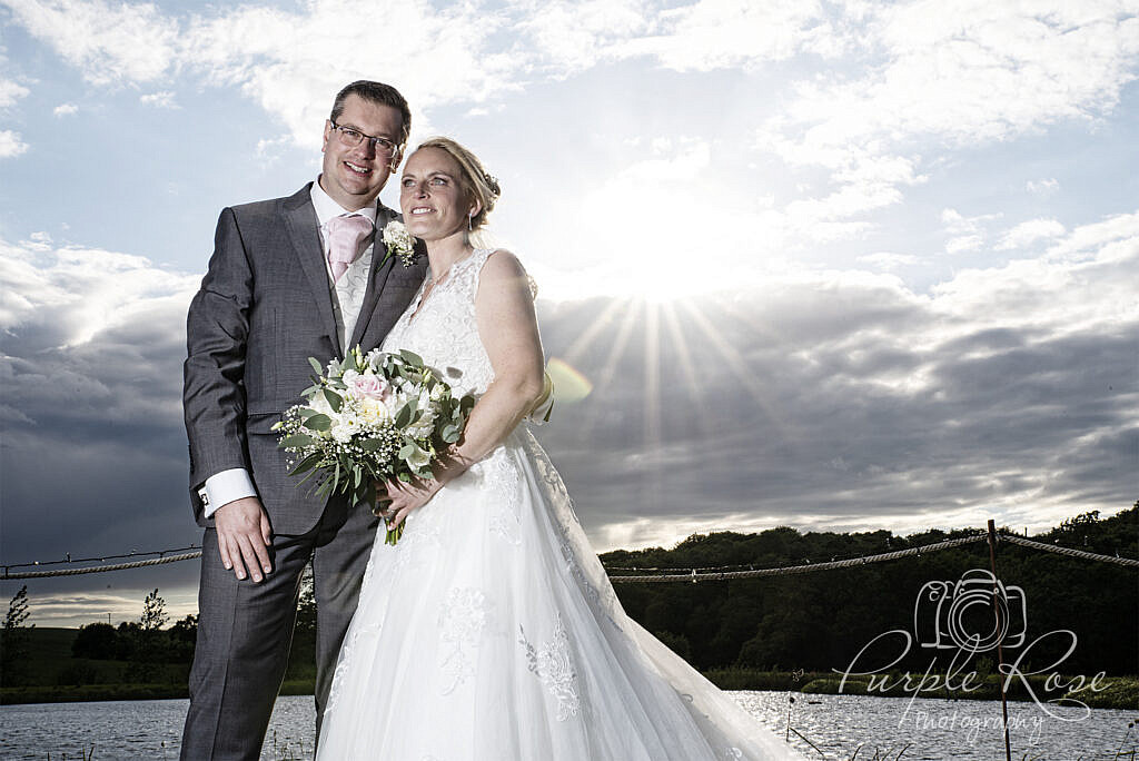 Photo of bride and groom with sun causing a star burst