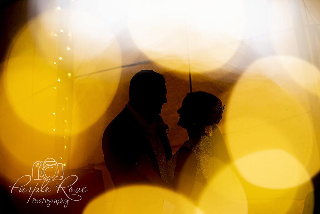 Silhouette of bride and groom dancing