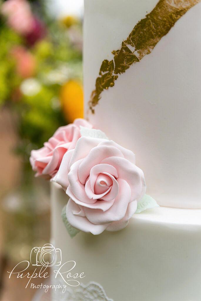 Pink sugar craft roses on a white wedding cake