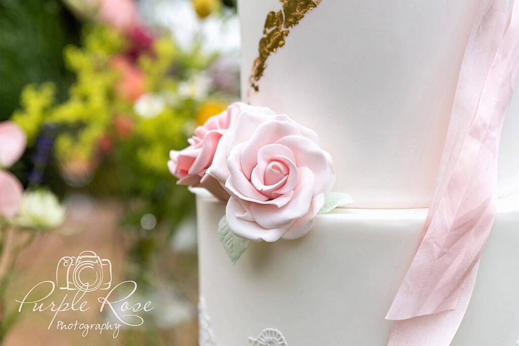 Pink and gold wedding cake close up