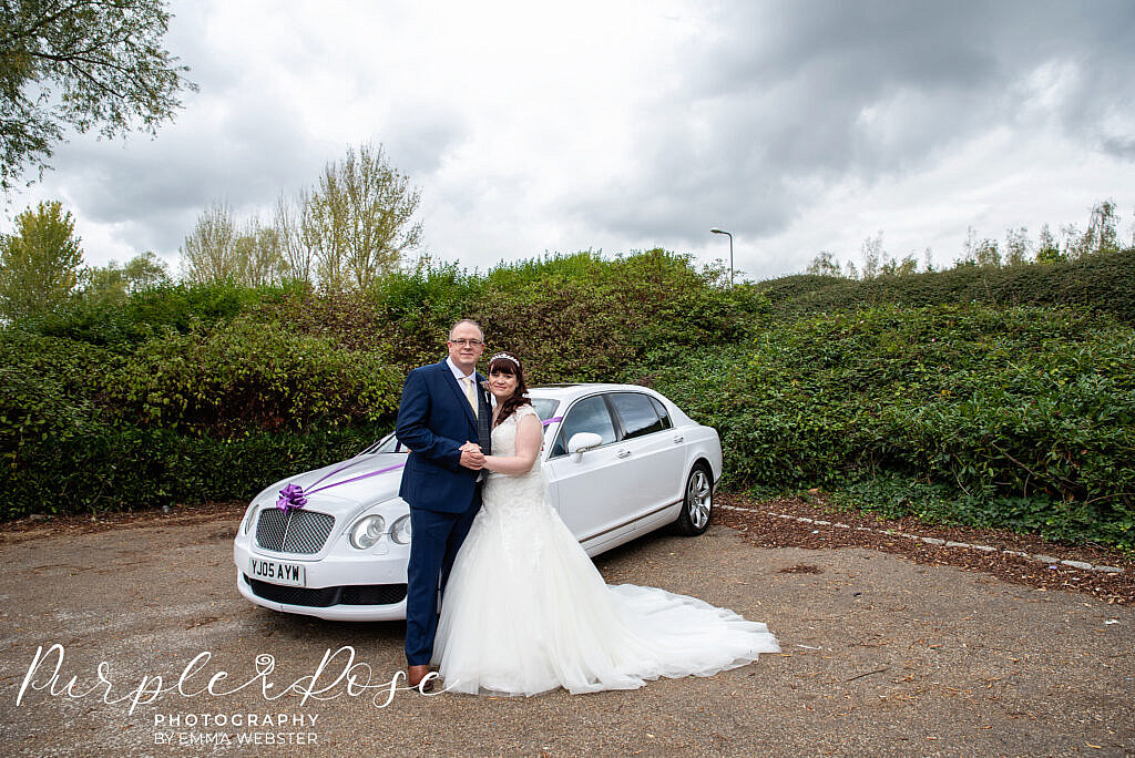 Bride and groom in front of their car