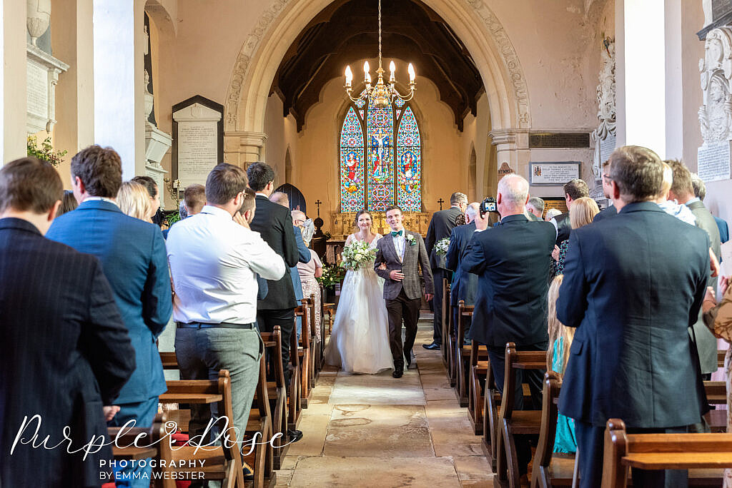 Bride and groom arm in arm leaving the church