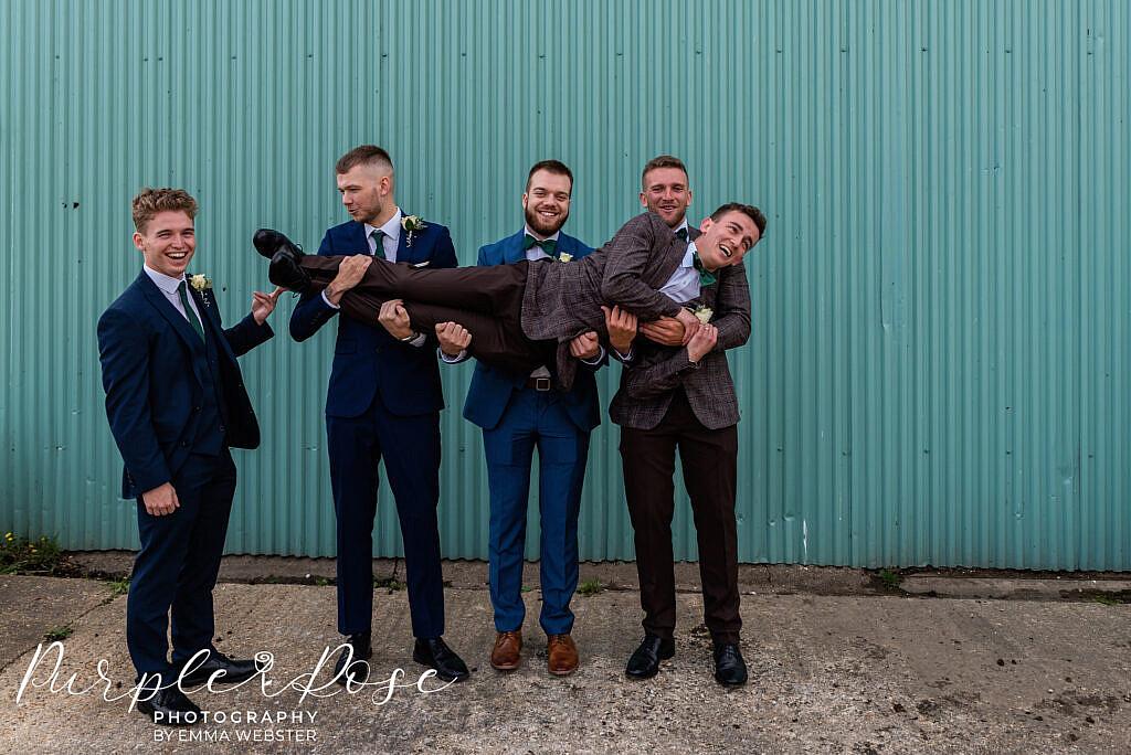 Groomsmen carry the groom