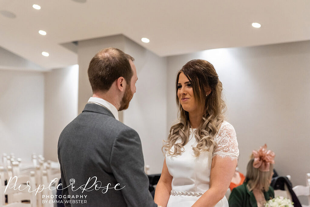 Bride smiling at her groom during the ceremony