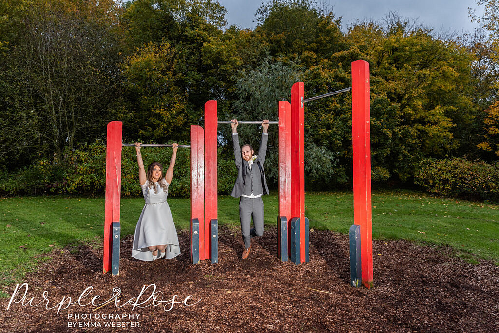 Bride and groom playing on a climbing frame