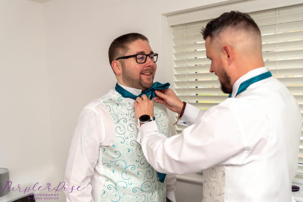 Best man adjusting grooms cravat