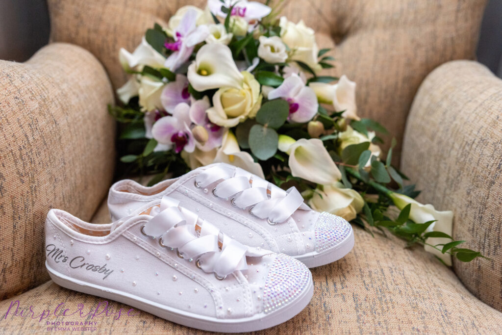 Brides bouquet and canvas trainers