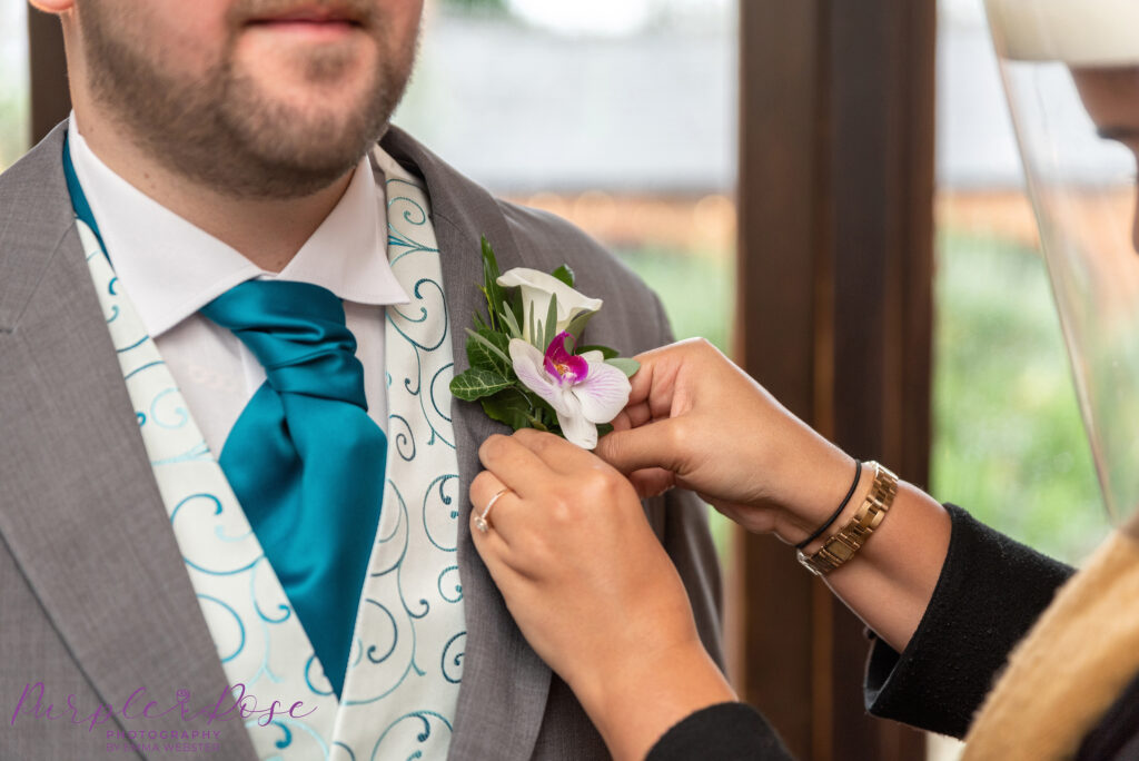 Groom having his buttonhole secured to his suit