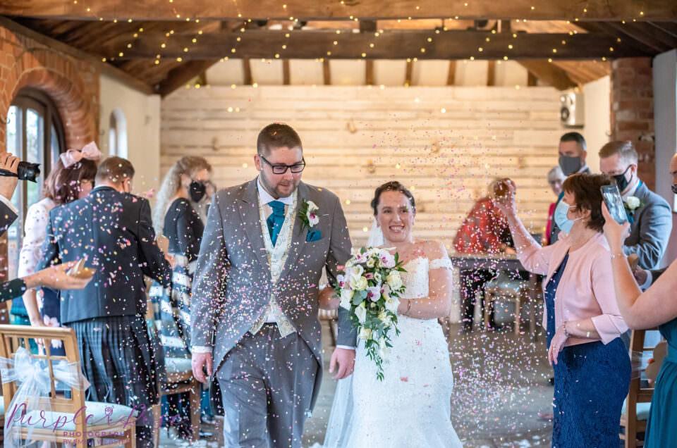 Bride and groom having confetti throne over them