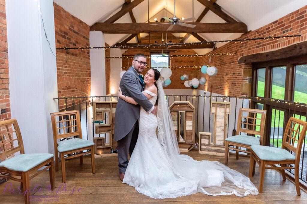 Bride and groom hugging a barn venue