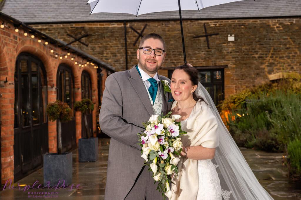 Bride and groom on a rainy wedding day