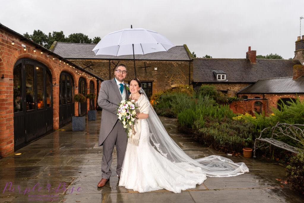 Bride and groom under an umbrella