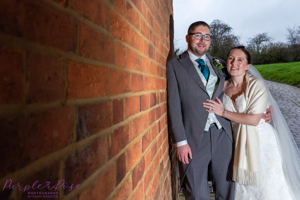 Bride and groom leaning on a wall