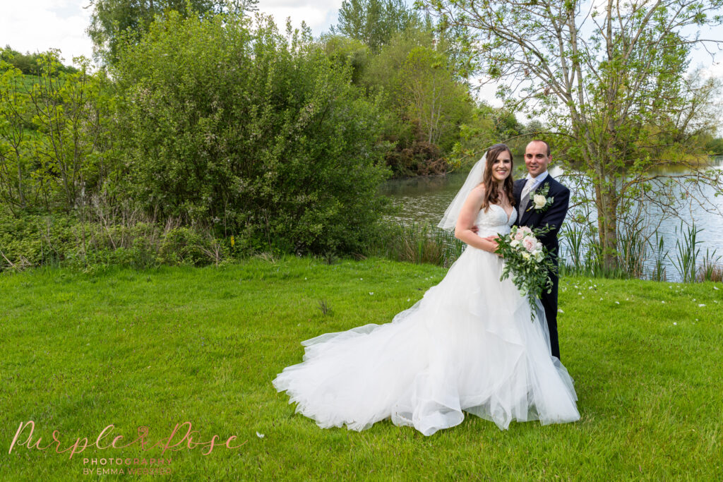 Couple in front of a lake on their wedding day