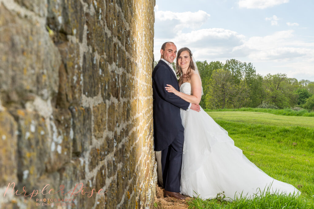 Bride and groom leaning on a brick wall