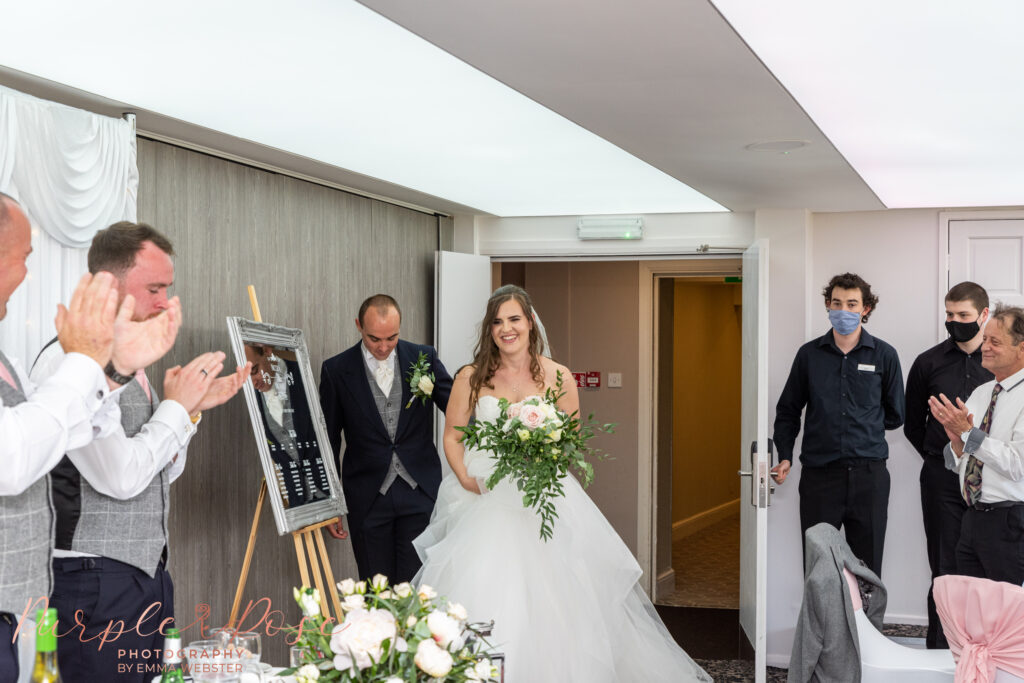 Bride and groom walking into their wedding reception