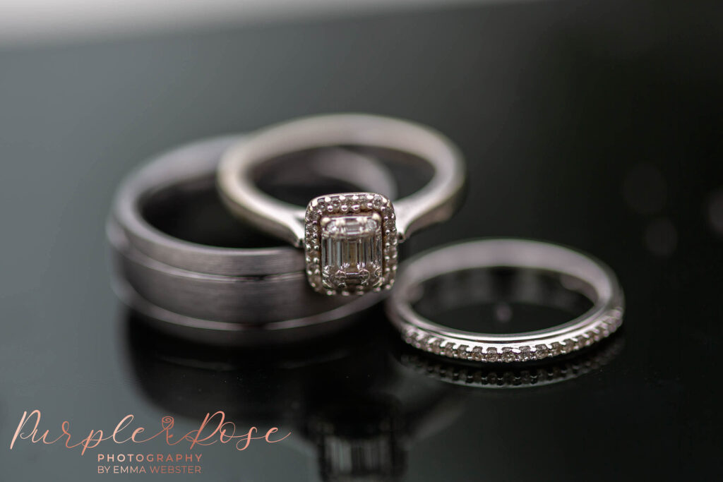 wedding and engagement rings on a reflective surface