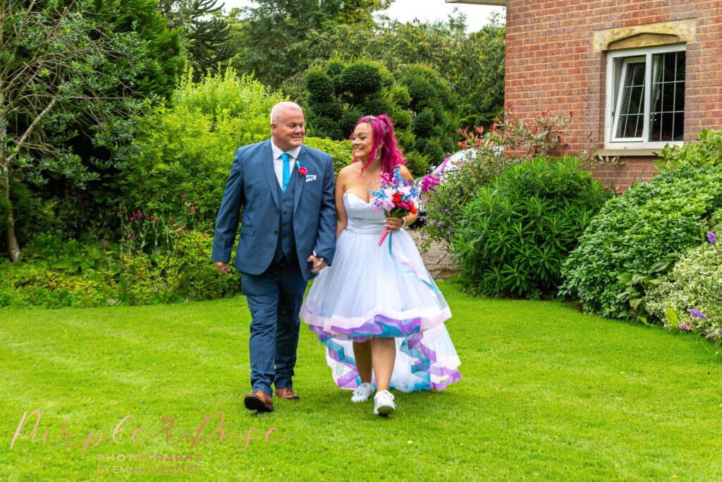 Bride walking through garden with her father