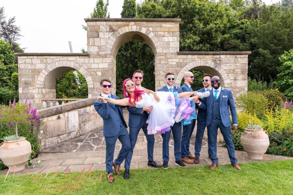 Groomsmen lifting bride
