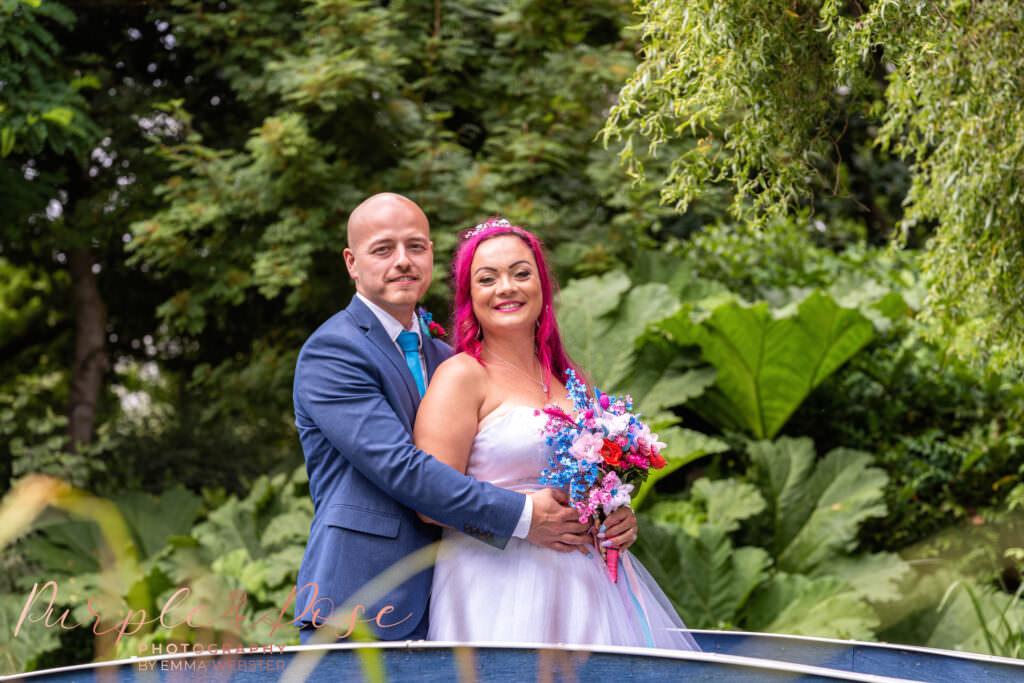 Bride and groom stood on a blue bridge