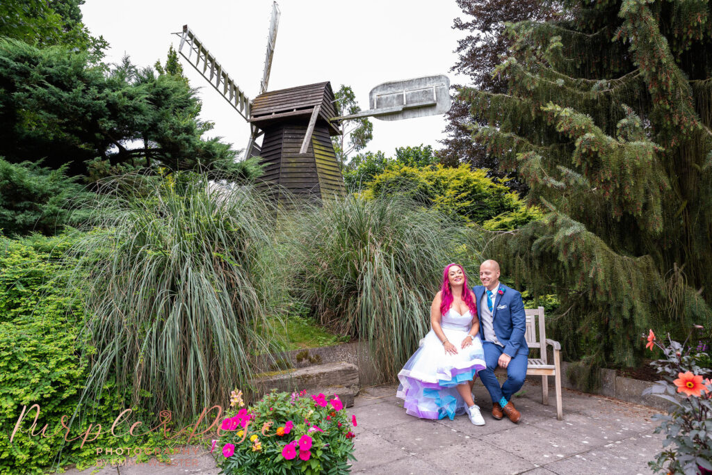 Bride and groom sat by a windmill