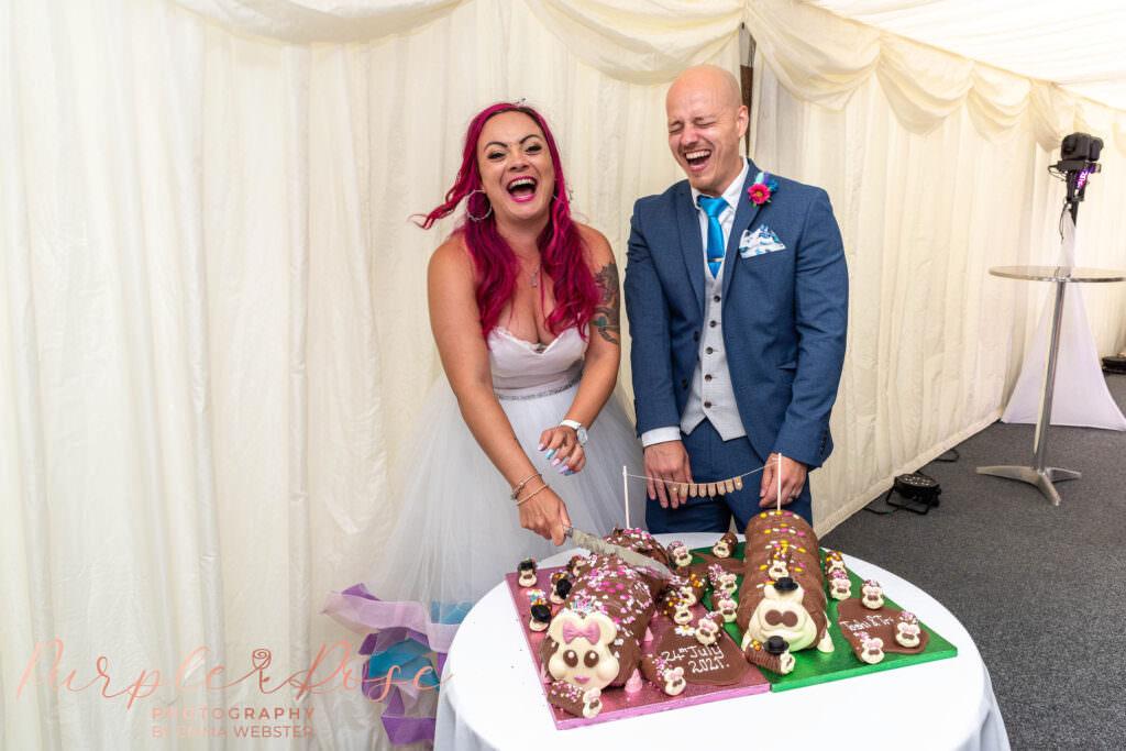 Bride and groom cutting caterpillar cakes