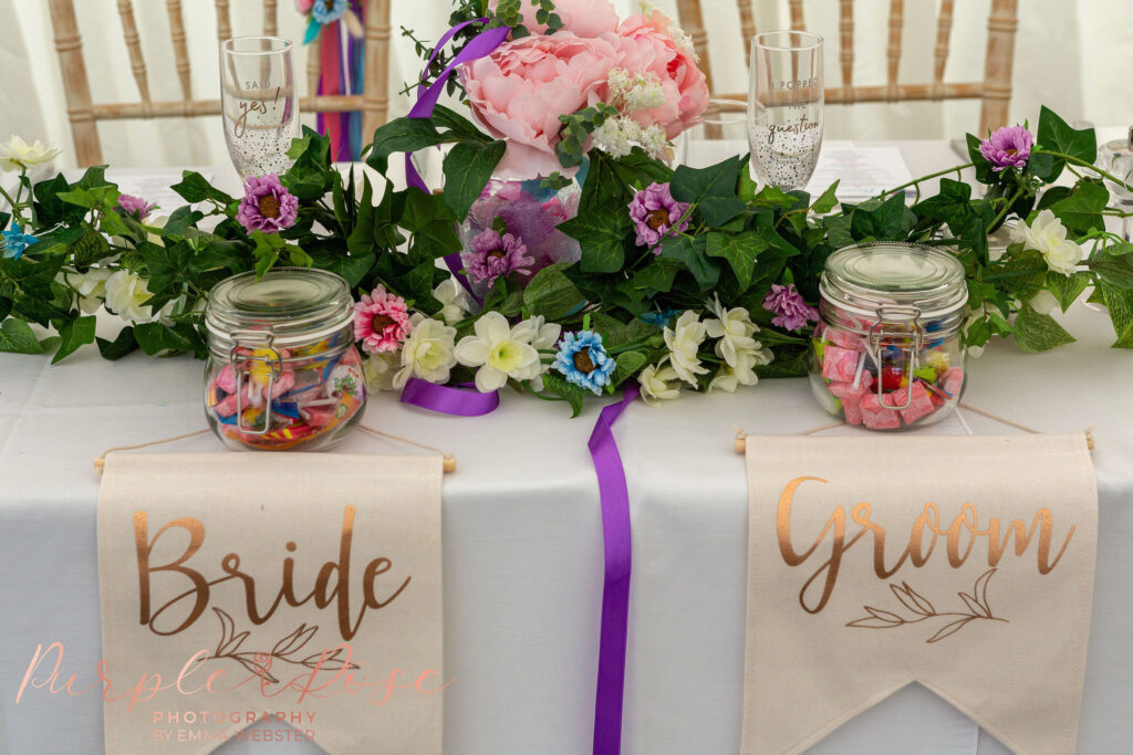 Head table with flowers and bride and groom sign
